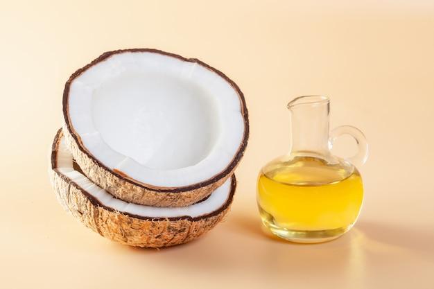 Noce di cocco con olio di cocco e foglie verdi della palma su terra arancio