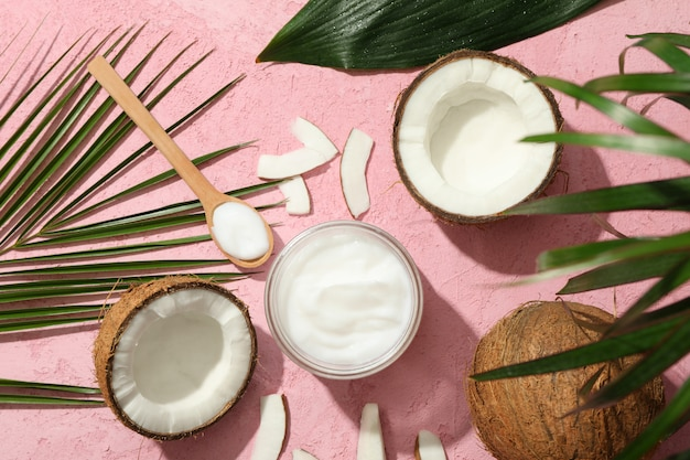 Noce di cocco e cosmetici sulla vista rosa e superiore