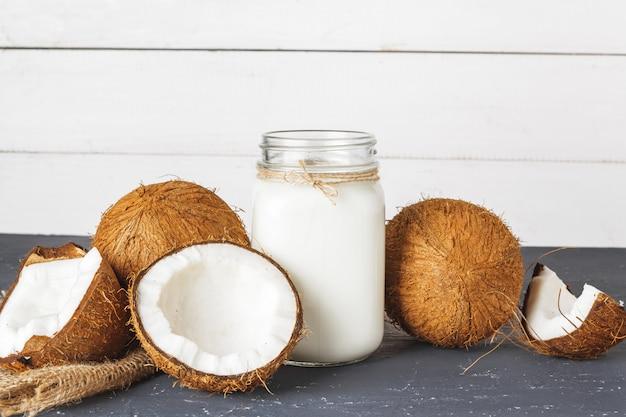 Noce di cocco e vetro di latte di cocco su fondo di legno