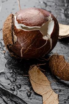 Noce di cocco matura rotta sul fondo nero della pietra dell'ardesia