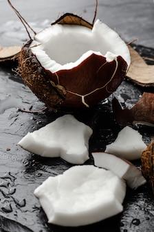 Noce di cocco mezza sul fondo nero della pietra dell'ardesia