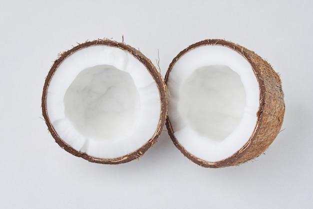Noce di cocco piena e metà incrinata su una superficie bianca, vista superiore