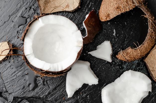 Noce di cocco rotta fresca mezza sul fondo nero dell'ardesia.