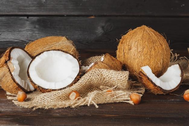 Noce di cocco rotta su una fine di legno invecchiata scura della tavola su