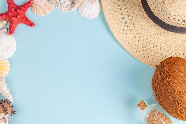 Noce di cocco, stelle marine, conchiglie, cappello di paglia e bottiglia con sabbia su fondo blu