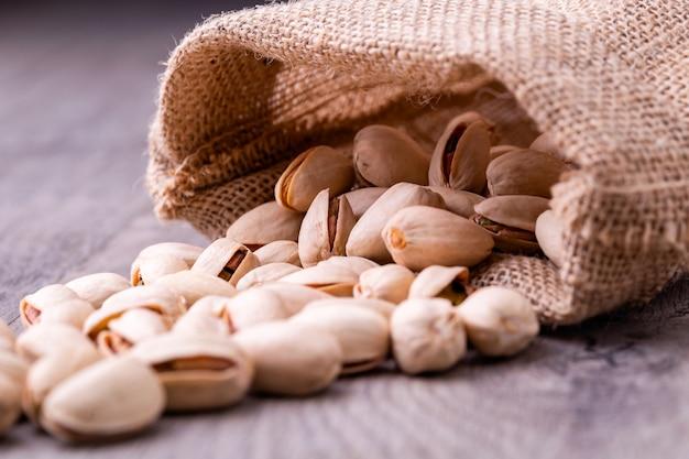Noce di pistacchi nel sacco di tela ruvida su fondo di legno granuloso.