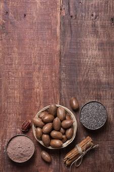 Noci americane, semi di chia e cacao in ciotole su una tavola di legno
