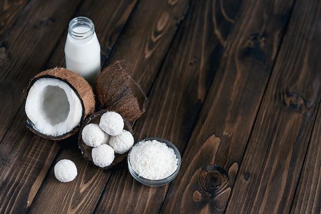 Noci di cocco con caramelle in scaglie di cocco e bottiglia di latte sul tavolo di legno.