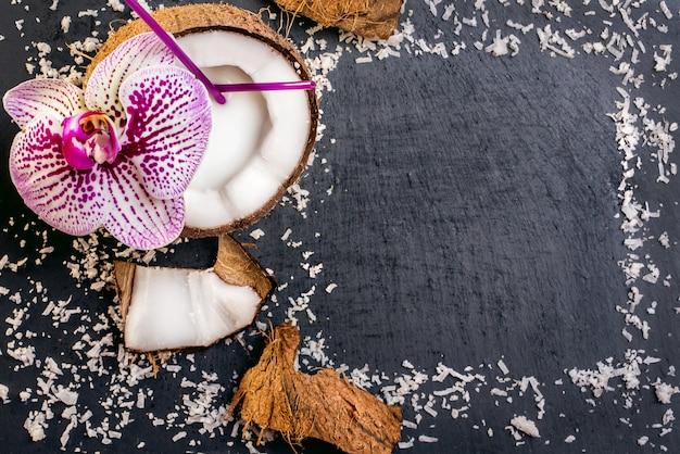 Noci di cocco con scaglie di cocco e orchidea sul backg pietra grigia