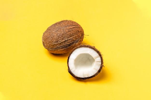 Noci di cocco mature e mezza noce di cocco su giallo brillante