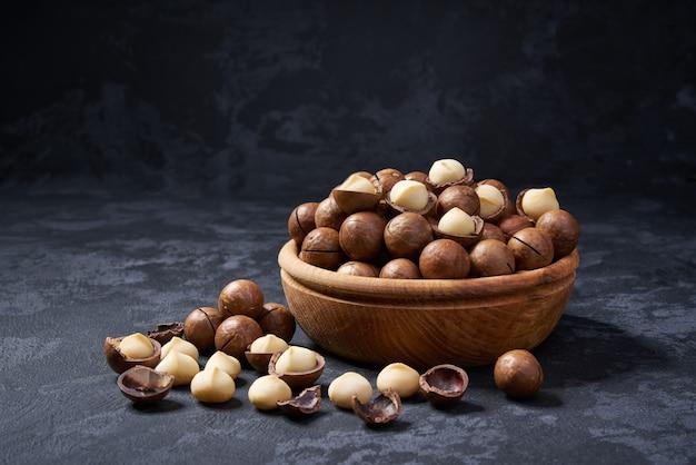 Noci di macadamia sgusciate e sgusciate in ciotola di legno sul nero, primo piano.