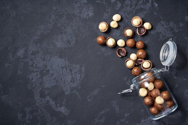 Noci di macadamia sgusciate e sgusciate in un barattolo di vetro aperto sulla tavola nera, con lo spazio della copia. vista dall'alto.
