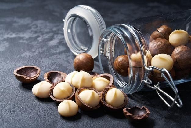 Noci di macadamia sgusciate e sgusciate in un barattolo di vetro aperto sulla tavola nera, primo piano.
