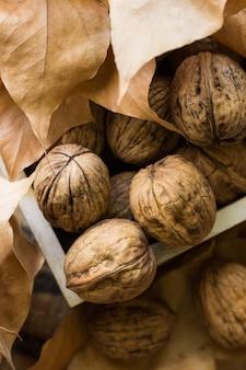 Noci intere in scatola di legno, foglie autunnali secche marroni.