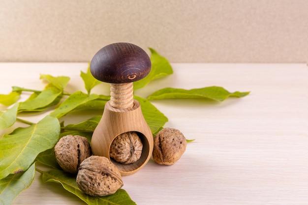 Noci intere sul tavolo di legno. noci e schiaccianoci in legno. ci piacciono le noci. pubblicità sulle noci
