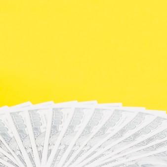 Noi banconote da cento dollari a ventaglio su sfondo giallo
