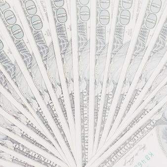 Noi banconote da cento dollari si aprono a ventaglio sullo sfondo