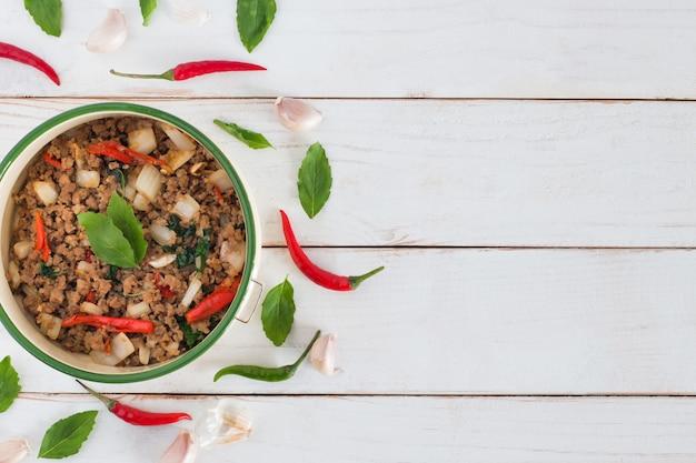 Nome pad ka prao dell'alimento tailandese, immagine di vista superiore della carne di maiale in padella con le foglie del basilico sulla tavola di legno bianca