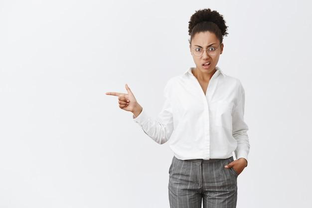 Non mi siederò in quella macchina. socio d'affari femminile afroamericano interrogato scontento in occhiali e camicia bianca, tenendosi per mano nei pantaloni, indicando a sinistra e fissando con antipatia e dubbio