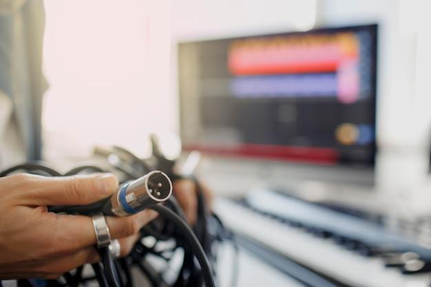 Non sa cosa fare con fili, corde e cavi. dj in studio televisivo. il produttore musicale sta componendo una canzone sulla tastiera del sintetizzatore e sul computer in studio di registrazione