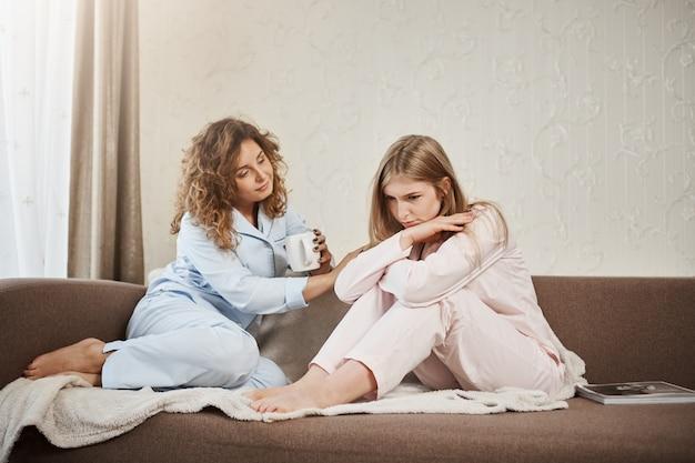 Non vale i tuoi nervi. ritratto di amichevole attraente ragazza dai capelli ricci caucasica seduto sul divano in indumenti da notte con un amico, cercando di confortare e rallegrare la triste donna, bere il tè
