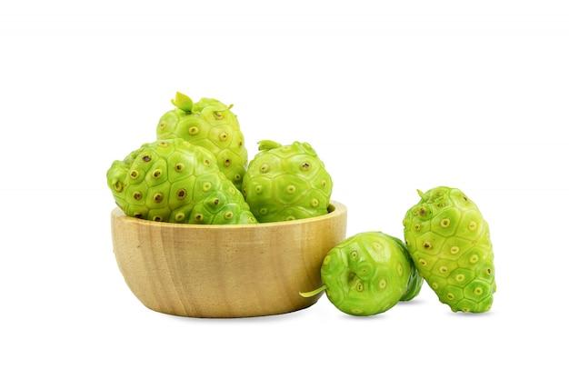 Noni o morinda citrifolia e pezzi in una tazza di legno, separati su uno sfondo bianco.