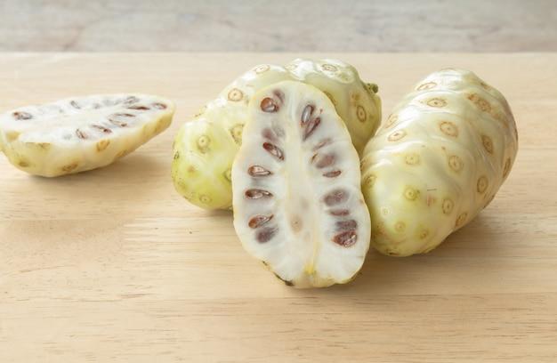 Noni o morinda citrifolia, grande morinda, gelso indiano, gelso di spiaggia, o frutta di formaggio sul tavolo di legno.
