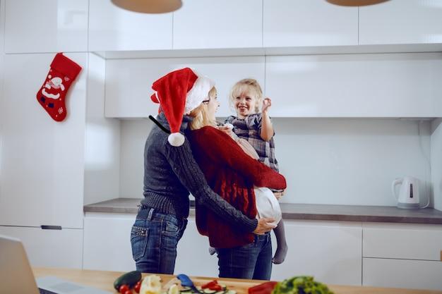 Nonna allegra, donna incinta e bambina che abbracciano nella cucina. sul bancone della cucina ci sono verdure e laptop. tempo di qualità per il concetto di natale.