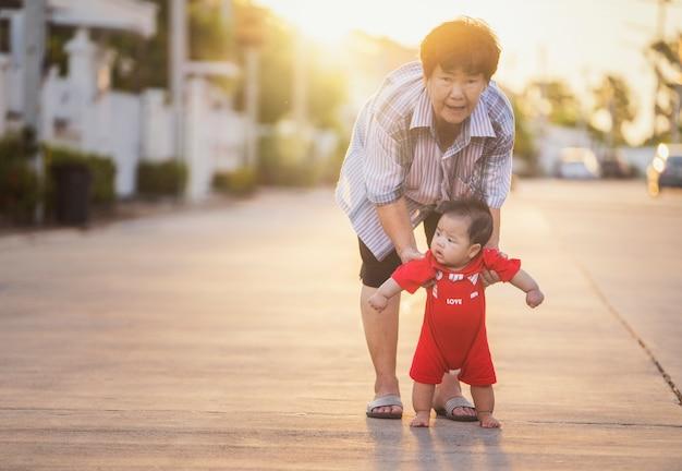 Nonna che aiuta tootler con l'allenamento a piedi