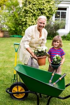 Nonna con i vasi da fiori della tenuta del ragazzo all'iarda