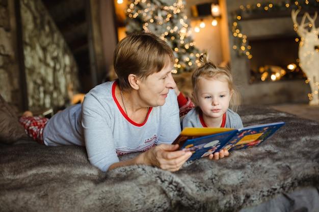 Nonna e nipote si divertono insieme a leggere un libro sul letto.