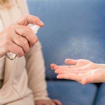 Nonna e ragazza del primo piano che usando disinfettante per le mani