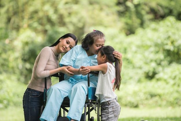 Nonna felice in sedia a rotelle con sua figlia e nipote in un parco, vita felice tempo felice.