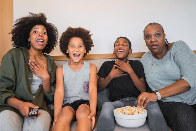 Nonna, madre e figli che guardano un film a casa.