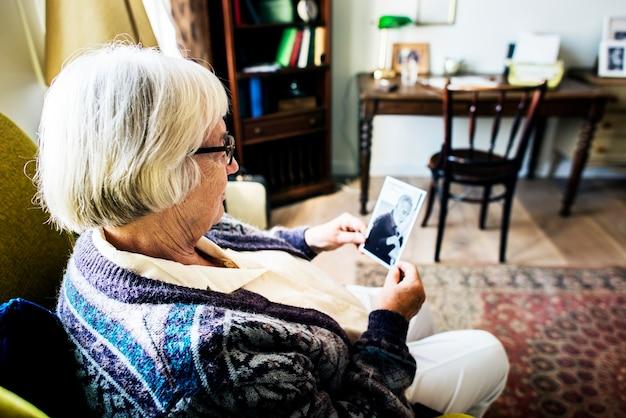 Nonna seduta e guardando la foto di suo marito