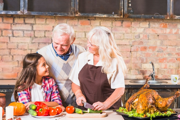 Nonni che cucinano tacchino con la nipote