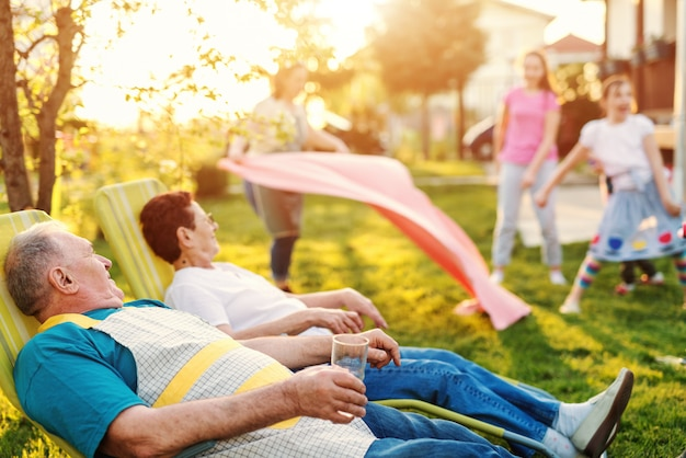 Nonni che si trovano e che riposano nel cortile. sullo sfondo i loro nipoti che giocano. concetto di riunione di famiglia.
