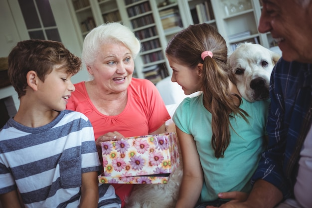 Nonni e nipoti che osservano il regalo di sorpresa in salone