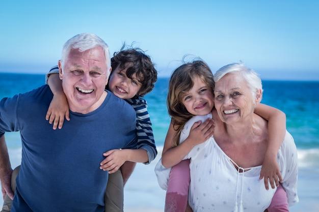 Nonni felici che danno sulle spalle ai bambini