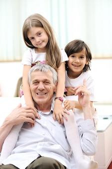 Nonno con bambini, uomo anziano a casa con la famiglia