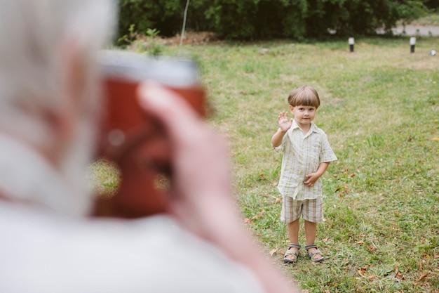 Nonno dell'angolo alto che prende foto del nipote