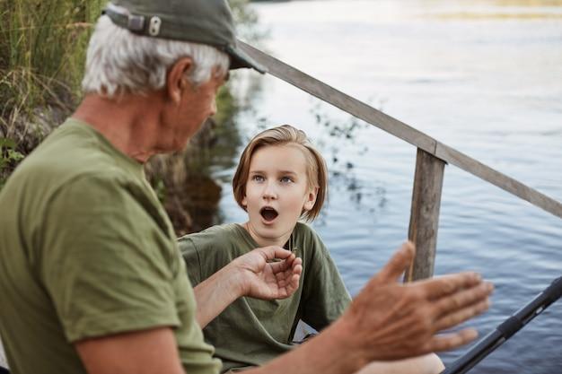 Nonno e nipote che pescano sull'ancoraggio del fiume, uomo anziano che mostra le dimensioni del pesce catturato l'ultima volta, figlio maschio che posa con la bocca aperta, scioccato.