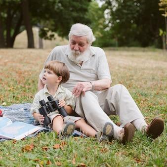 Nonno e nipote in parco con binocolo