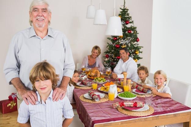 Nonno e nipote in piedi accanto al tavolo da pranzo