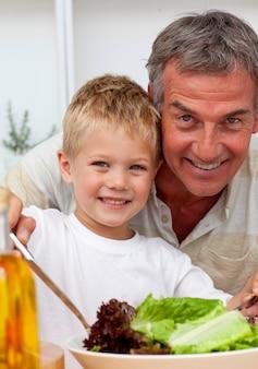 Nonno felice che cucina un'insalata con il nipote