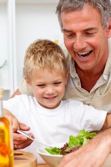 Nonno felice che mangia un'insalata con il nipote