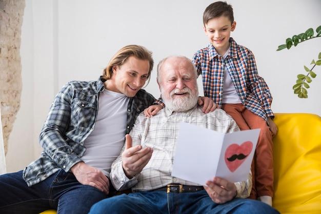 Nonno felice che osserva attraverso la cartolina d'auguri fatta a mano