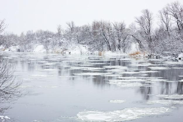 Nonno fluttuante sul fiume d'inverno, paesaggio invernale, alluvioni primaverili