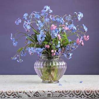 Nontiscordardime blu e rosa (myosotis). piccolo mazzo di fiori in un vaso di vetro su uno sfondo viola.