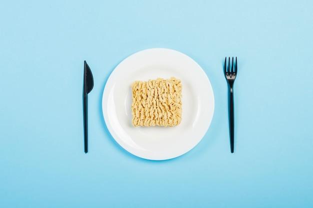 Noodles istantanei asiatici e piatti monouso in plastica su una superficie blu. il concetto di cibi pronti, fast food, cibo spazzatura. vista piana, vista dall'alto.